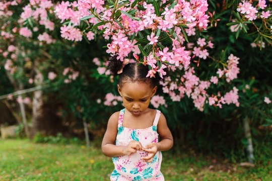 child looking at flower